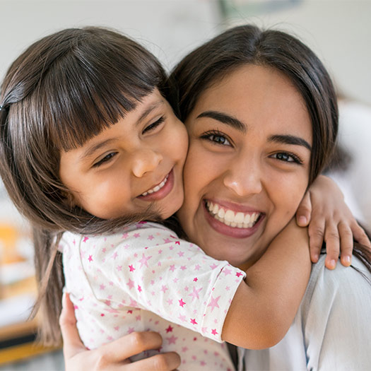 A mother and daughter hugging with big smiles on their faces