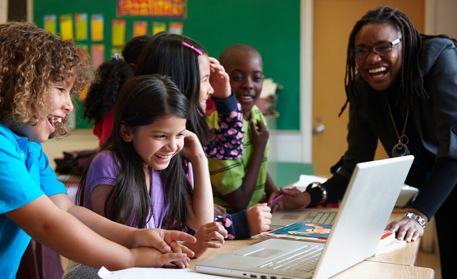 Children in a group watching a laptop with joyful expressions